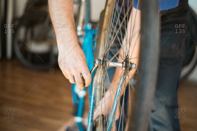 Man putting bike tire onto a bike frame and tightening the bolts