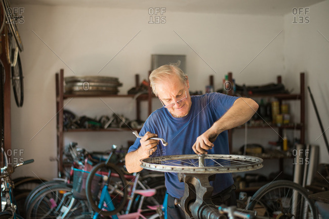 Man loosening bolt on a bike tire with a bench vise