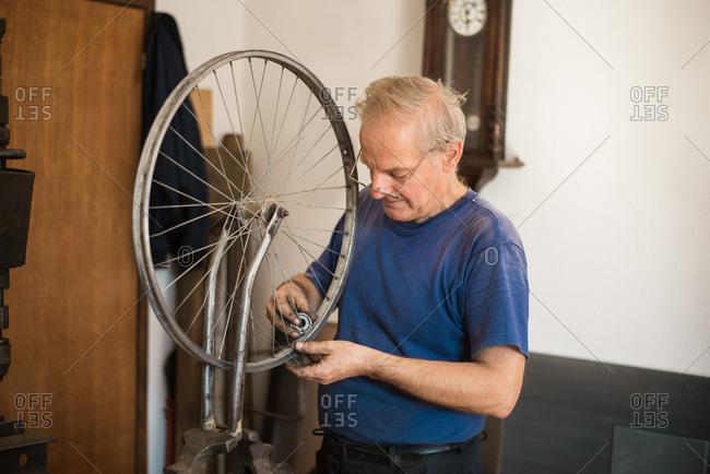 Man repairing bicycle wheel rim in his shop