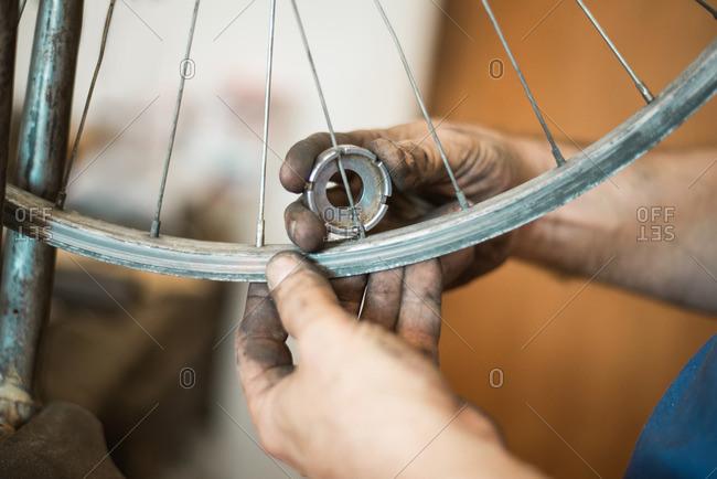 Man repairing bicycle wheel with a spoke nipple key
