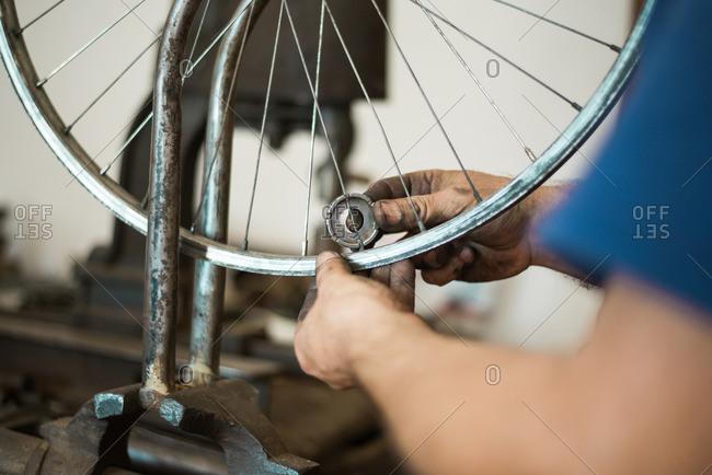 Man repairing bicycle wheel spokes in his shop