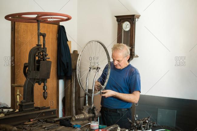Man repairing bike wheel spokes in his workshop