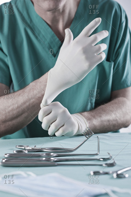 A surgeon puts on his gloves