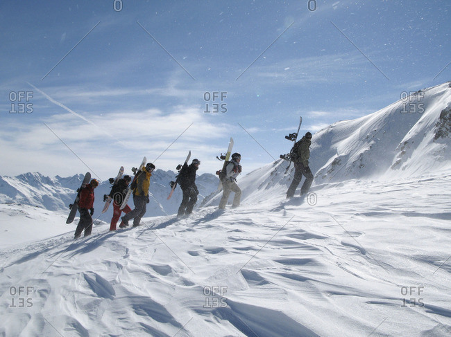 Group of snowboarders ascending snowy mountain
