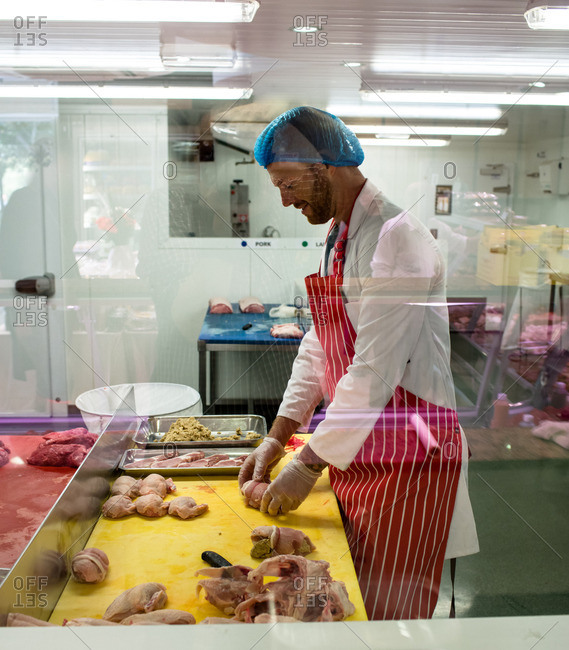 Butcher preparing a chicken and steak roll in butchers shop