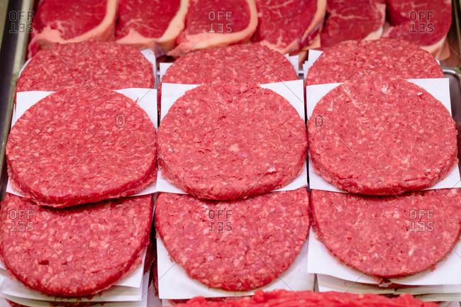 Close-up of raw hamburger patties on display