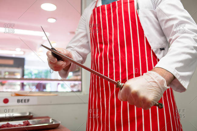 Mid section of butcher sharpening his knife in butchers shop
