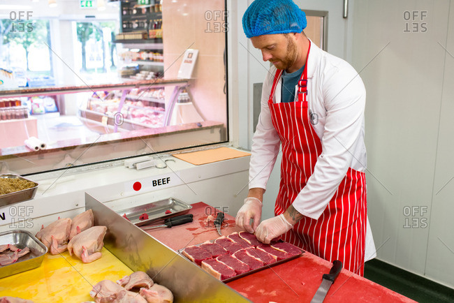 Butcher arranging steaks in tray at butchers shop