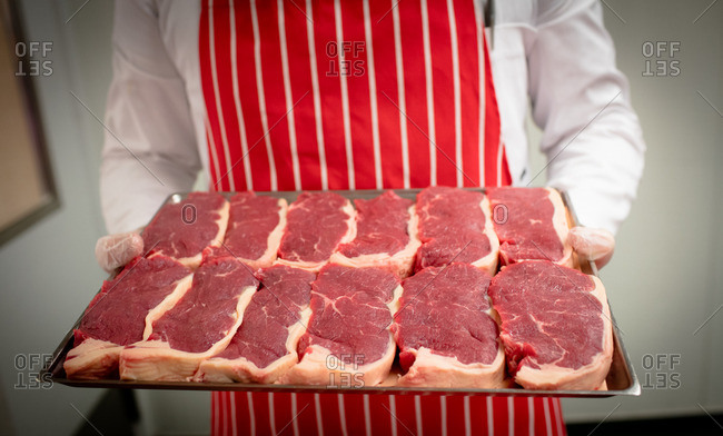 Mid section of butcher holding a tray of steaks at butchers shop