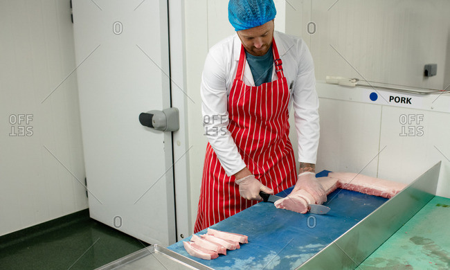 Butcher slicing meat at butchers shop