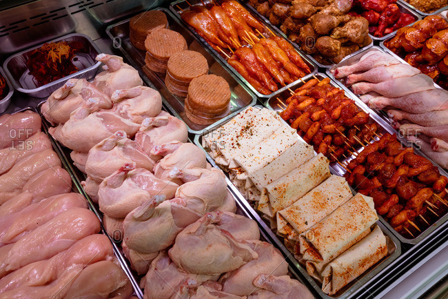 Variety of marinated meat at display counter in butchers shop