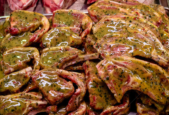 Marinade meat at display counter in butchers shop
