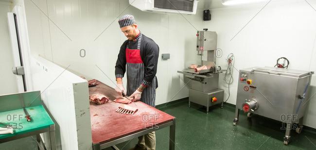 Butcher cutting pork ribs in butchers shop