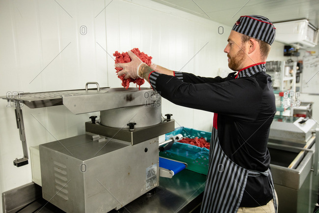Butcher putting meat in mincer machine at butchers shop