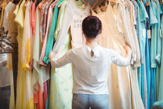 Woman selecting a clothes from hanger at boutique store
