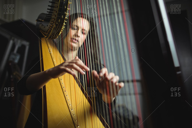 Attentive woman playing a harp in music school