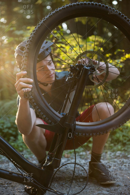 Male cyclist repairing his bicycle in forest on a sunny day