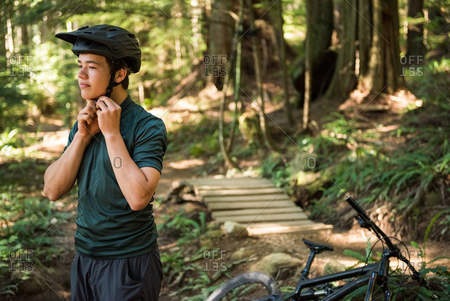 Male athletic wearing bicycle helmet in forest