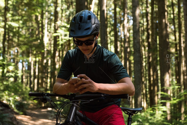 Male cyclist using mobile phone in forest on a sunny day