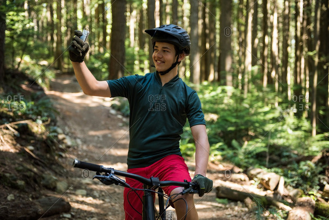 Male cyclist taking selfie on mobile phone in forest