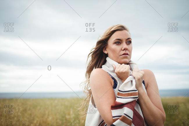 Woman standing in the field feeling the breeze