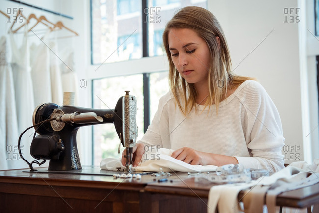Female dressmaker sewing on the sewing machine in the studio