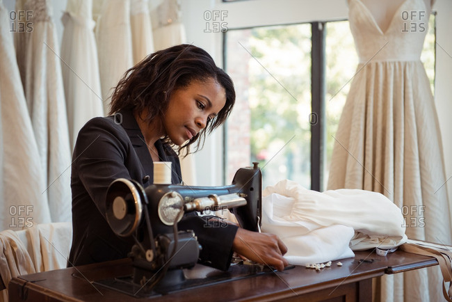 Fashion designer sewing on the sewing machine in the studio