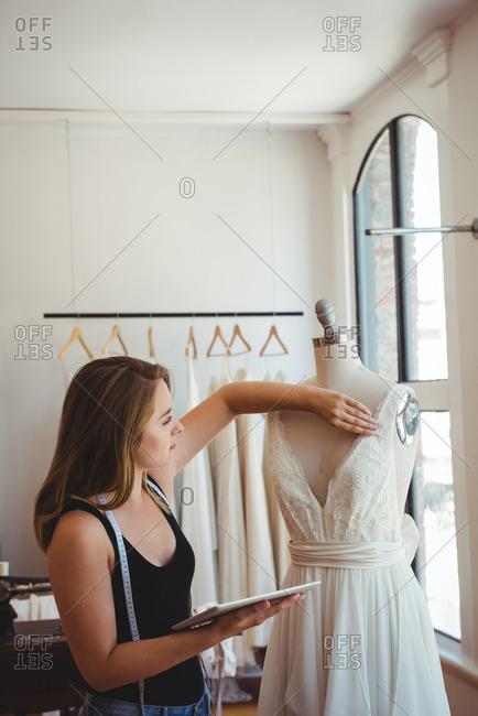 Female fashion designer adjusting the dress on a mannequin in the studio