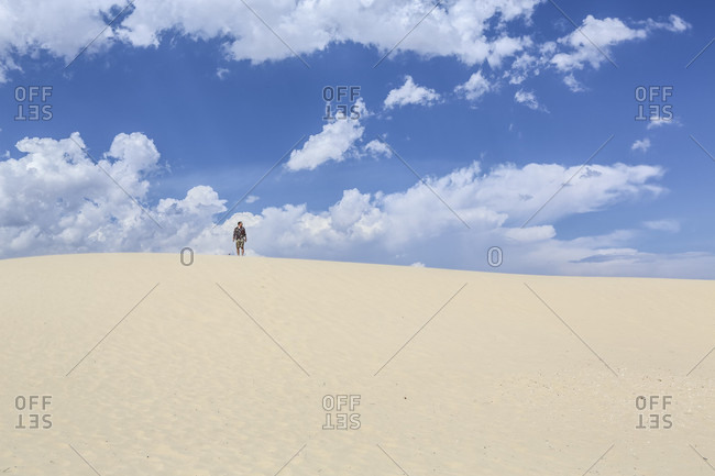 Monahan's State Park, Texas, United States - May 27, 2013: A young man stands under a dramatic sky in a sandy desert at Monahan's State Park in Texas