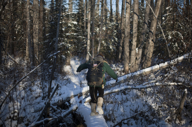 Dawson City, Yukon Territory, Canada - October 28, 2014: A man crosses a creek to get to his off-the-grid cabin in the Yukon Territory