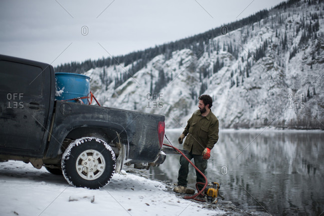 Yukon River, Yukon Territory, Canada - October 29, 2014: Guy Couture collects house-hold water from the Yukon River in West Dawson, Yukon Territory