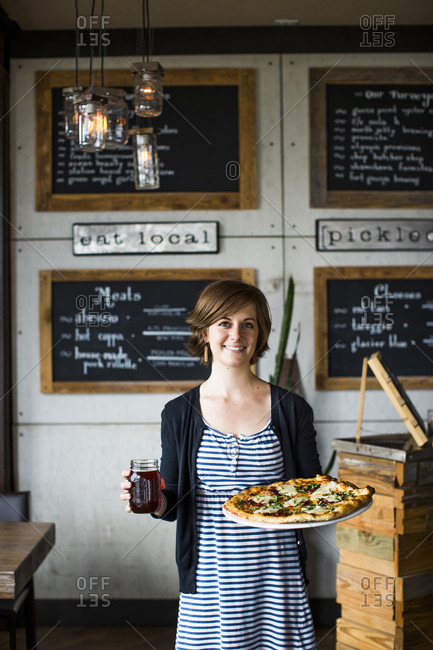 Long Beach, WA, USA - July 6, 2014: A young woman serves pizza and beer at a restaurant