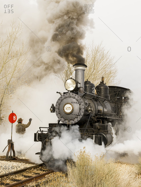 Carson City, Nevada, USA - December 15, 2012: Man waves to steam train as it leaves the station, Nevada State Railroad Museum