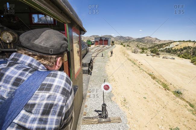Virginia City, Nevada, USA - June 3, 2012: Steam train Engineer Brian Covey looks on as he drives train toward  engine house.  Virginia & Truckee Railroad