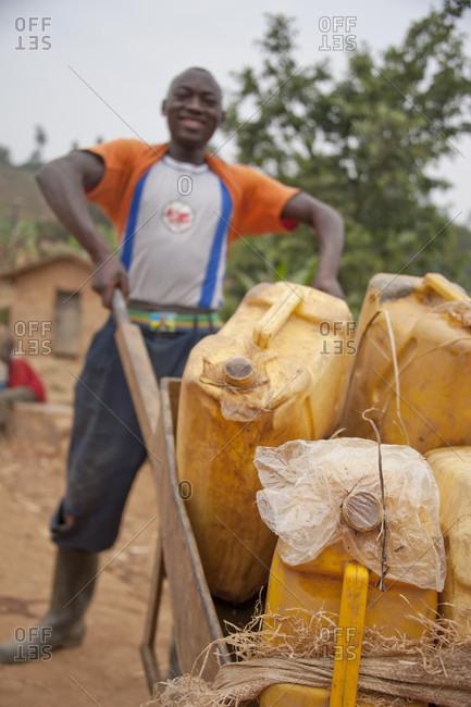 Rulindo, Rwanda - August 11, 2011: A young man hauls jugs of drinking water in a wheelbarrow in Rulindo, Rwanda