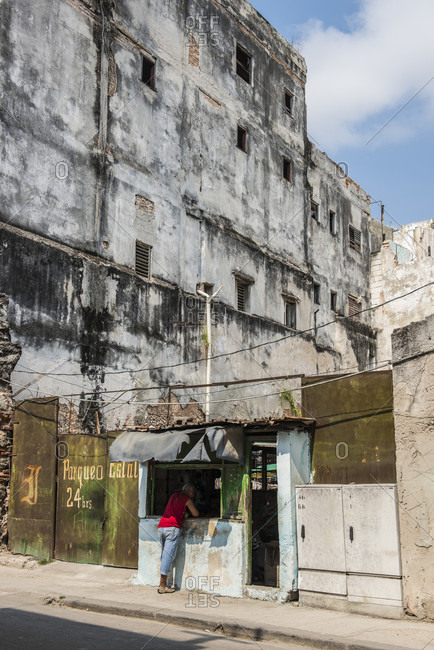 Havana, La Habana, Cuba - October 5, 2016: Beneath crumbling buildings, a man in a red shirt stands at the counter of a small street-side parking office. Havana Centro, La Habana, Cuba