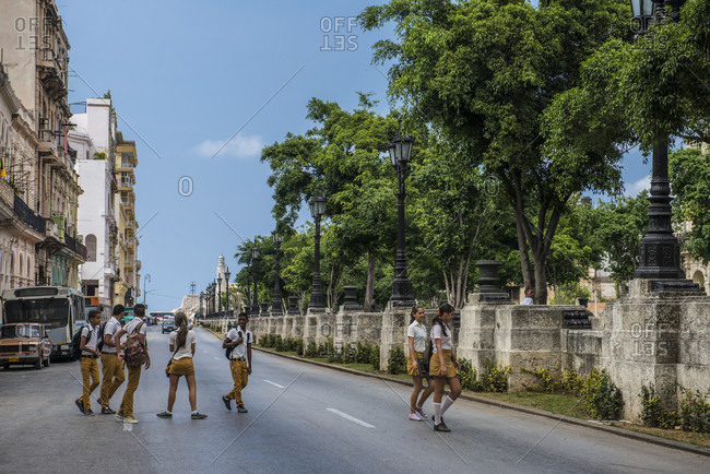 Havana, La Habana, Cuba - October 5, 2016: A group of Cuban teens in school uniforms walking across the El Prado Boulevard (Paseo del Prado) toward the Paseo Marti, Havana's famous tree lined promenade. Havana Centro, La Habana, Cuba Havana, La Habana, Cuba