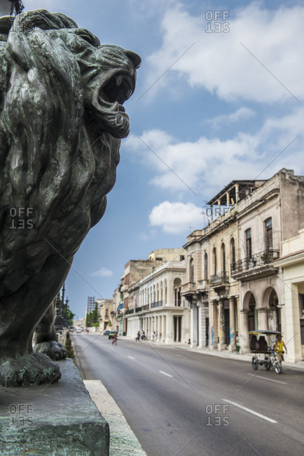 Havana, La Habana, Cuba - October 5, 2016: A bronze lion guards historic buildings at El Prado Boulevard (Paseo del Prado), a famous landmark in Havana. This famous street's neocolonial style includes marble benches, baroque street lamps, and these popular bronze lions. Havana Centro, La Habana, Cuba