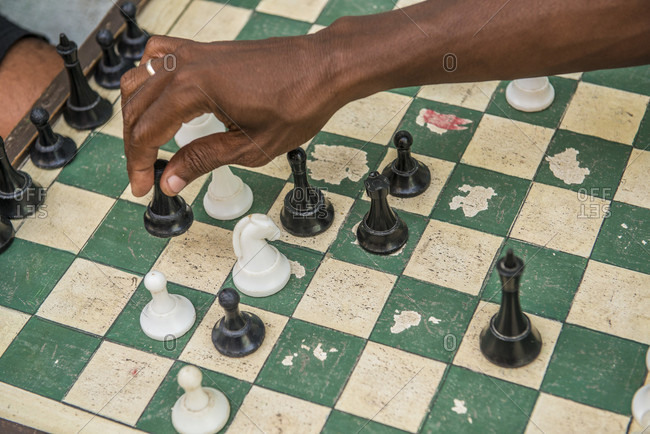 Havana, La Habana, Cuba - October 5, 2016: The arm of a Cuban man playing street chess, seen from above. Street chess is very popular in Cuba. In fact, Cuba is ranked 17th in the world by the World Chess Federation. Havana Centro, La Habana, Cuba