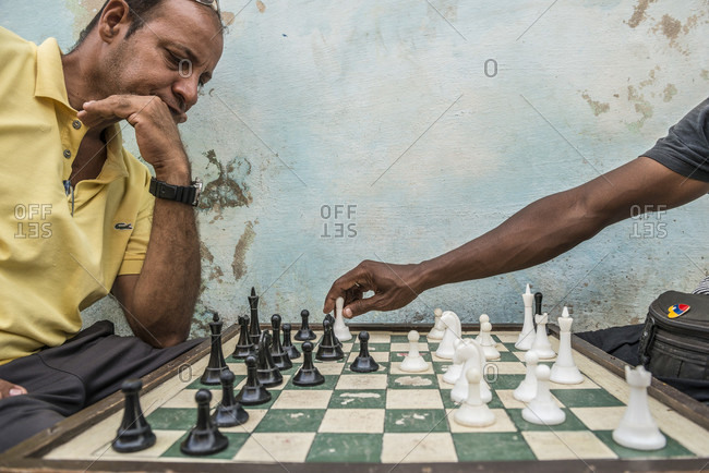 Havana, La Habana, Cuba - October 5, 2016: Two Cuban men playing street chess. One man finishes his move, and the other ponders. Street chess is very popular in Cuba. In fact, Cuba is ranked 17th in the world by the World Chess Federation. Havana Centro, La Habana, Cuba