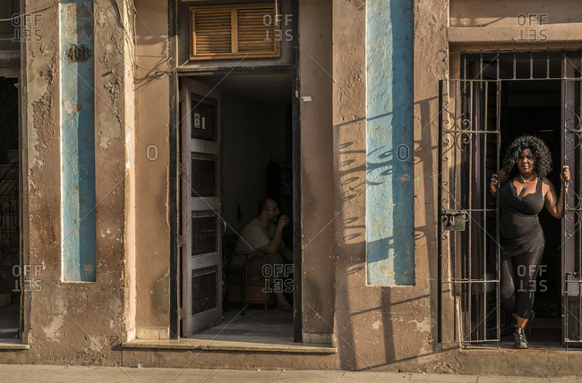 Havana, La Habana, Cuba - October 5, 2016: An Afro-Cuban woman leans out of her doorway on a Havana street. A bearded man can be seen in the shadows of the adjacent door. Havana Centro, La Habana, Cuba