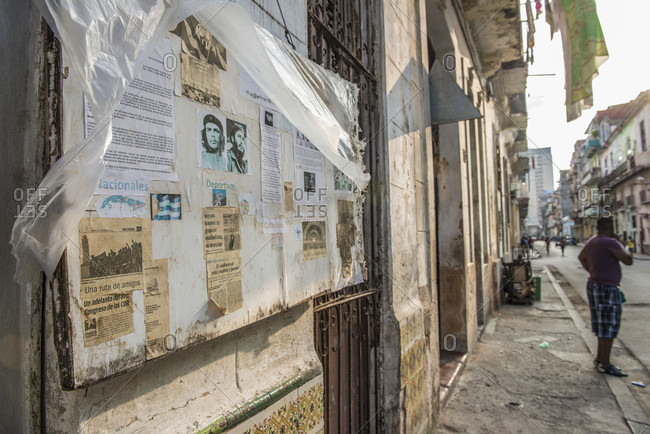 Havana, La Habana, Cuba - October 5, 2016: A tattered community bulletin board on the sidewalk. National news (Nacionales), Sports news (deportivas), Events, and the requisite portrait of Ernesto 'Che' Guevara and Fidel Castro in the center. Havana Centro, La Habana, Cuba