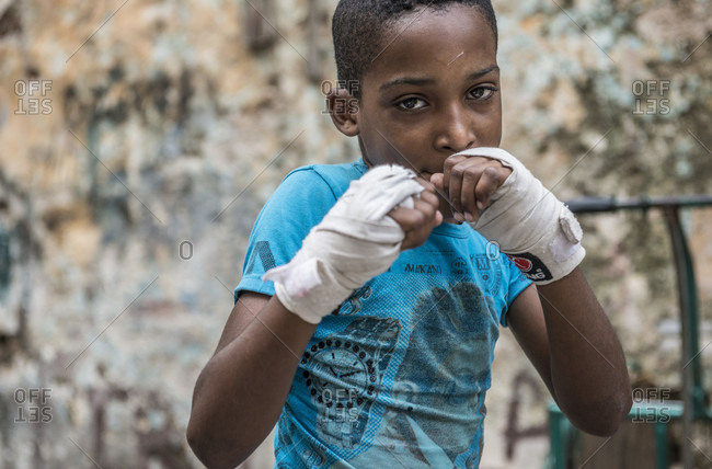 Old Havana, La Habana, Cuba - April 24, 2014: A serious young Cuban boy takes a sparring stance, wearing boxing wraps. Project Cuba Boxeo, an aid project from Malaika Aid for Children, the creation of Samuel 'Sammy' Fabbri. The organization brings boxing to Cuban children from 8-21 years of age.  The boxing ring sits between a group of crumbling buildings between Calle San Jose and Calle Aguila, in Old Havana or Habana Vieja, La Havana, Cuba