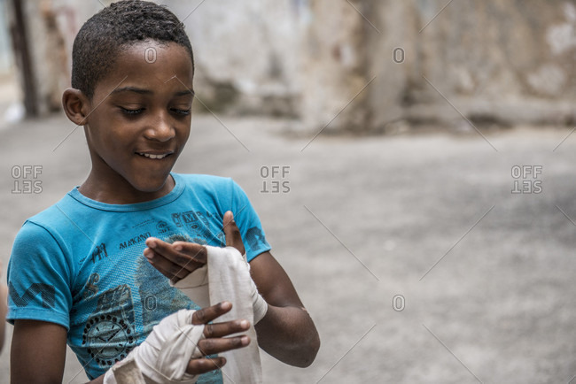 Old Havana, La Habana, Cuba - April 24, 2014: A young Cuban boy looks happy with his boxing wraps as he prepares for sparring at Project Cuba Boxeo, an aid project from Malaika Aid for Children, the creation of Samuel 'Sammy' Fabbri. The organization brings boxing to Cuban children from 8-21 years of age. The boxing ring sits between a group of crumbling buildings between Calle San Jose and Calle Aguila, in Old Havana or Habana Vieja, La Havana, Cuba