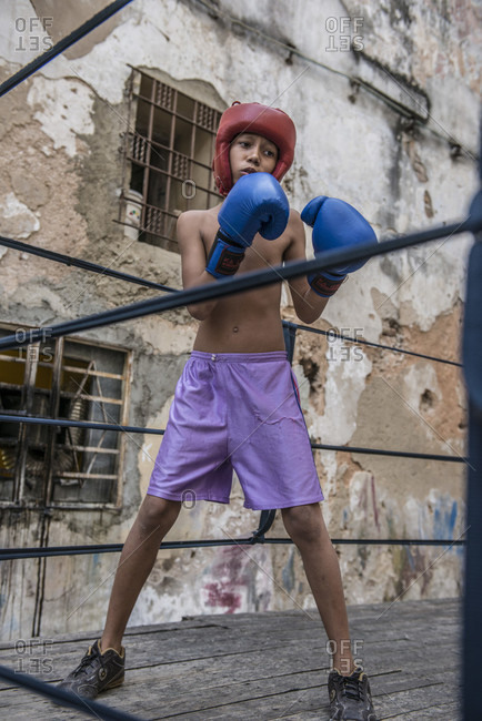 Old Havana, La Habana, Cuba - April 24, 2014: Low angle view of a young Cuban boy wearing blue gloves and red headgear, sparring at Project Cuba Boxeo, an aid project from Malaika Aid for Children, the creation of Samuel 'Sammy' Fabbri. The organization brings boxing to Cuban children from 8-21 years of age. The boxing ring sits between a group of crumbling buildings between Calle San Jose and Calle Aguila, in Old Havana or Habana Vieja, La Havana, Cuba