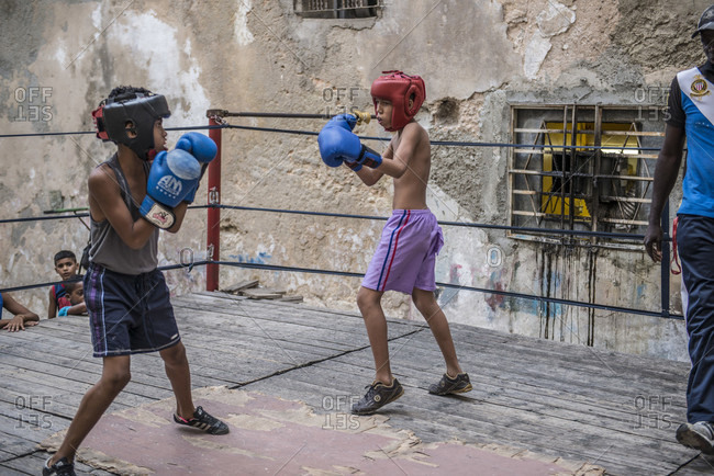 Old Havana, La Habana, Cuba - April 24, 2014: Two boys sparring on the makeshift ring at Project Cuba Boxeo, an aid project from Malaika Aid for Children, the creation of Samuel 'Sammy' Fabbri, who is seen coaching in this photo. The organization brings boxing to Cuban children from 8-21 years of age. The boxing ring sits between a group of crumbling buildings between Calle San Jose and Calle Aguila, in Old Havana or Habana Vieja, La Havana, Cuba