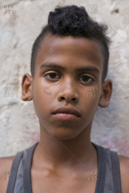 Old Havana, La Habana, Cuba - April 24, 2014: Portrait of a serious young Cuban boy leaning against a wall at Project Cuba Boxeo, an aid project from Malaika Aid for Children, the creation of Samuel 'Sammy' Fabbri. The organization brings boxing to Cuban children from 8-21 years of age. The boxing ring sits between a group of crumbling buildings between Calle San Jose and Calle Aguila, in Old Havana or Habana Vieja, La Havana, Cuba