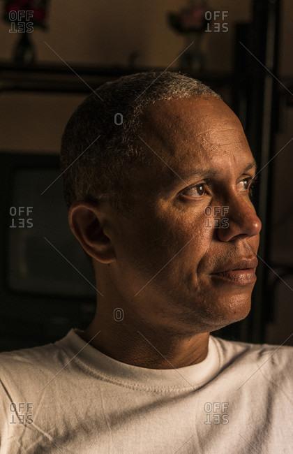 Havana, La Habana, Cuba - April 25, 2014: Portrait of a young Afro Cuban man wearing a white shirt. His face is illuminated by soft window light. Centro Havana, La Habana, Cuba