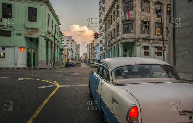 Havana, La Habana, Cuba - April 25, 2014: Colonial and modern buildings meet at the intersection of Galiano and San Lazaro in Centro Habana. A vintage 50's Chevy waits at the traffic light  in the foreground. Sunset. Havana, La Habana, Cuba