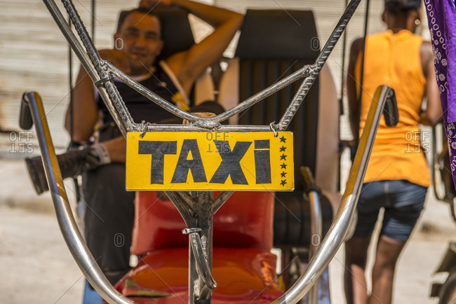 "Old Havana, La Habana, Cuba - April 25, 2014: The handlebars of a Cuban Bicitaxi with a hand-painted ""TAXI"" sign hanging from them. The driver relaxes in the back seat of the cab, waiting for his next fare. The bicycle taxi is a Cuban icon, often homemade from scrap parts. Old Havana or Habana Vieja, La Habana, Cuba"